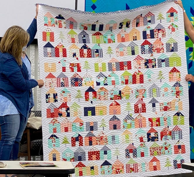Members of Big Red Quilters' Guild pose for a photo with a new quilt. In total, the group has donated more than 100 quilts in 2020 and 2021.