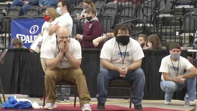 Assistant coach Tim Parsons (left), head coach Matt Smith (middle) and assistant Jared Hughes (right) look on during Monday action at the 74th annual West Virginia High School State Wrestling Tournament at Huntington's Mountain Health Arena.