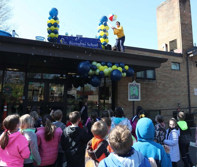 Erin Faetanini, the principal of St.Barnabas School, hits a beach ball to students from the school's roof during their recess on April 19.