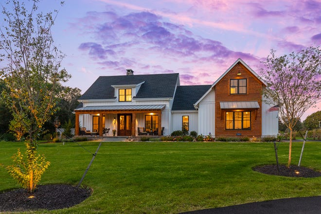 A cedar bay and porch break up the white board-and-batten facade, adding a modern twist to the home's archetypal farmhouse design.