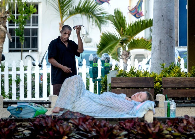 A man cuts his hair as a woman sleeps by the Great Lawn and Lake Pavilion in downtown West Palm Beach Tuesday morning, July 16, 2019.