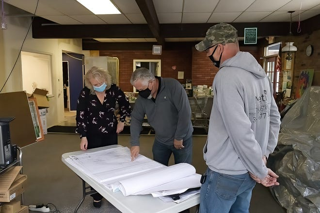 Metis Construction President Julie Brandle, left, goes over plans for a renovation at Kent Social Services with Project Manager Rollin Gedney, center, and Joe Yost, the working superintendent. Supply chain issues have made the renovation a little trickier than it would have been otherwise.