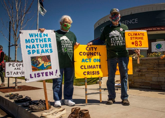 """Pat Allen, left, and Mike Allen stand together holding their signs, including one that notes this is their 83rd climate strike. Mike said that they're always protesting together, """"never one without the other"""" in their green Volkswagen Beetle."""