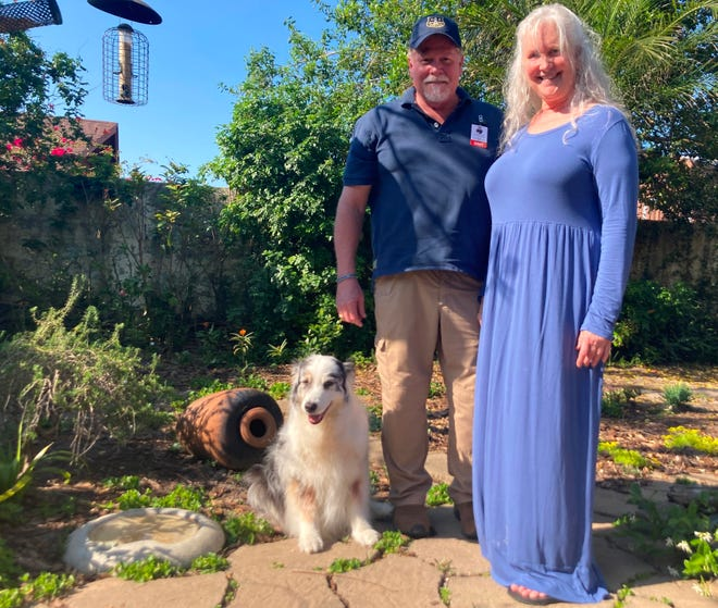 Rick and Rosanne Cain stand with their Australian shepherd, Chessi, in their Anastasia Island backyard on Monday. The couple nurture plants that attract monarch butterflies and a wealth of birds and other wildlife. A monarch butterfly, lots of caterpillars, a tufted titmouse and other creatures visited the property on Monday.