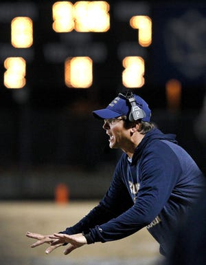 Burns football coach David Devine communicates with his team during their 2019 playoff matchup with North Lincoln.