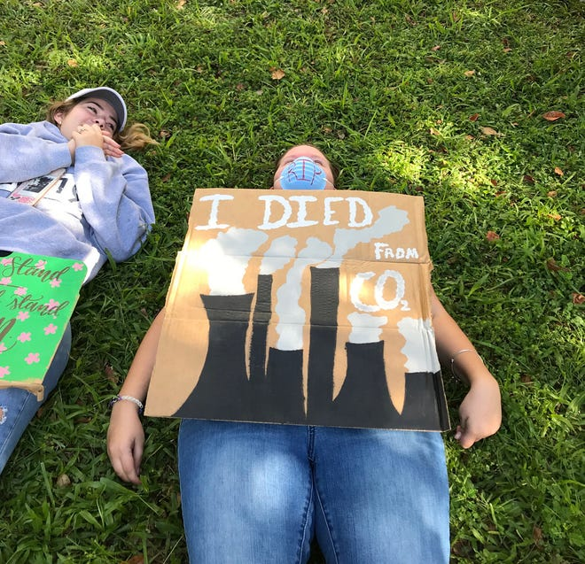 """Activists held a """"die in"""" organized by by 350 Wilmington on Sept. 20, 2019, at Wilmington City Hall to protest a lack of action to combat climate change. Some displayed signs saying how they """"died."""""""