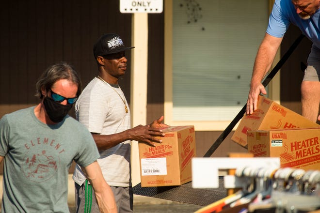 Volunteers unload and distribute clothes and food items during Havelock's Operation Outpost – an outreach event held every first Wednesday of the month in the afternoon by the Religious Community Services of New Bern (RCS). Other events are held in Bridgeton, Pollocksville and Alliance.