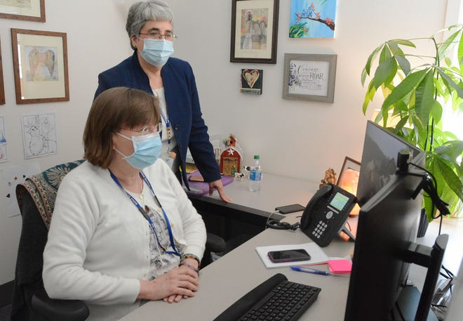 Diane Manning, president/CEO of United Services in Dayville,  standing ,works with crisis team member Elaine Gazzola, MSW Tuesday at the behavioral mental health center. [John Shishmanian/ NorwichBulletin.com]