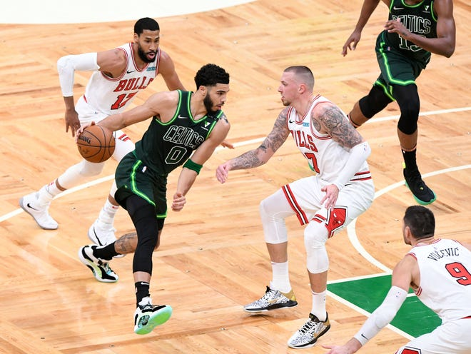 Celtics forward Jayson Tatum drives to the basket on Bulls center Daniel Theis during the first half Monday night at the TD Garden.