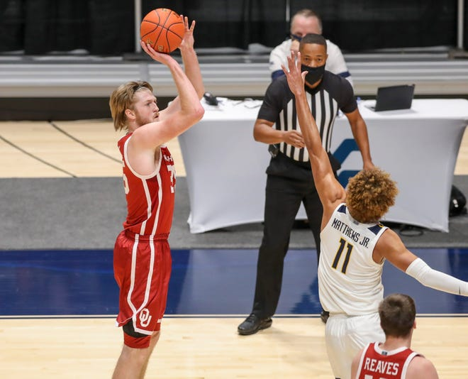 Former Oklahoma forward Brady Manek (35), who will play at UNC as a graduate transfer for the 2020-21 season, shoots a 3-pointer against West Virginia during a Feb. 13, 2021, game at WVU Coliseum in Morgantown.