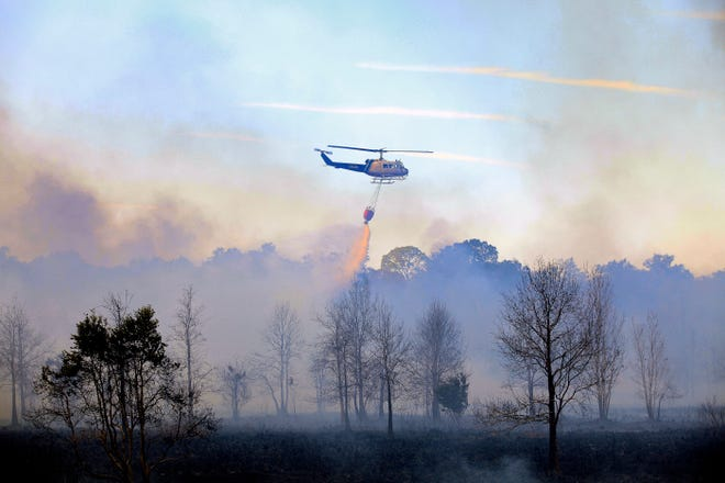 A helicopter douses a three-day old wildfire with retardant over Lochloosa Prairie near Cross Creek in December 2010. [The Gainesville Sun/File]