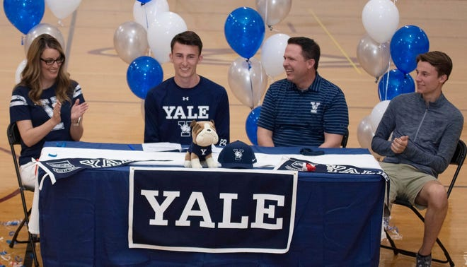 Oak Hall's Austin Montini, second from left, signed with the Yale Bulldogs in a ceremony Monday at the school's gymnasium with family by his side.