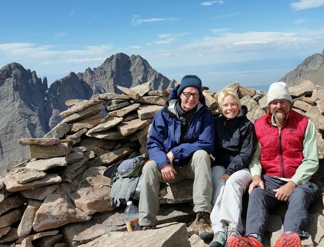 Jill Mattoon, center, sits with Ron Toretta, left, and Ed Biery, right, at the top of Humboldt Peak in Custer County, CO