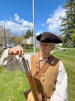 Richard MacKay a long-time member of the Billerica Colonial Minute Men, stood on the Billerica Town Common, on Monday, April 19, Patriot's Day. Here he is preparing his musket.