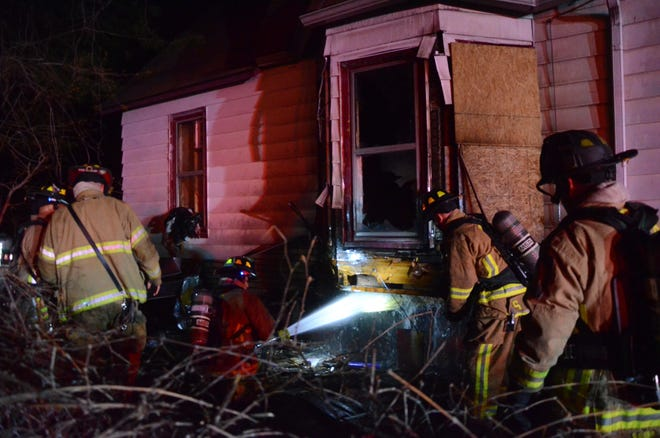 Battle Creek firefighters douse a fire set on the outside of 203 Post Ave. Tuesday morning. A second fire was reported after firefighters left.