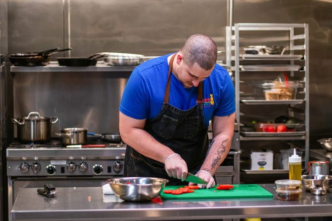 "Chef Cody Nash-Gibney slices tomatoes for his fresh pico de gallo for his final dish,  as seen on ""Chef Boot Camp."""