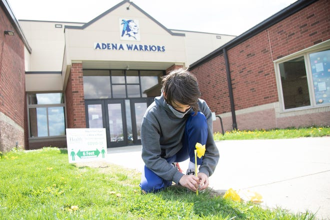 Logan Whitley puts yellow windmills in the ground at one of Adena Local Schools entrances for the National Month of Hope. Whitley, along with several other classmates, started a Hope Squad to help create a safe environment for their classmates and help fight against mental illness.