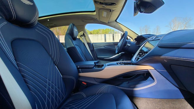 The gorgeous interior of the 2021 Aston Martin DBX includes blue leather seats and a single-pane panoramic sunroof.