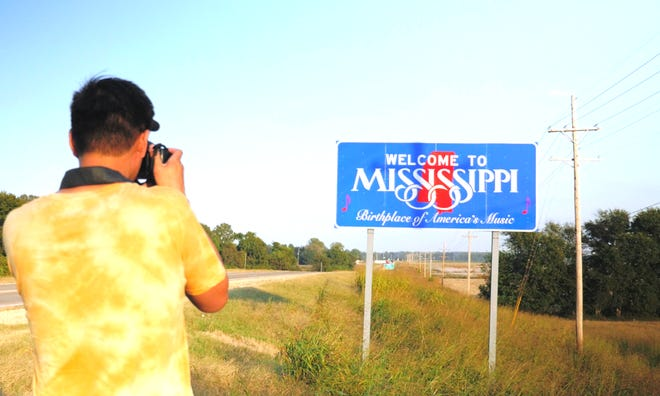"""Baldwin Chiu, producer and lead subject in the documentary """"Far East Deep South"""" takes of picture of the Mississippi border."""