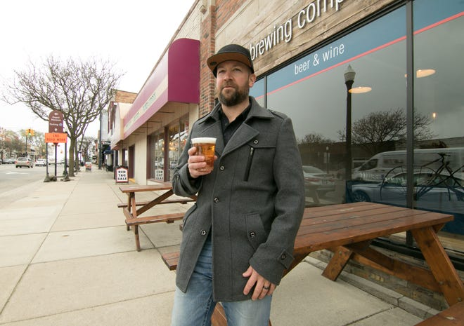 Co-owner Clark Gill sits outside his brew pub Aberrant Ales in downtown Howell Tuesday, April 20, 2021. Gill may look into getting a permit for a social district in Howell.