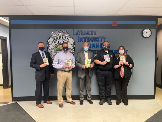 (From left to right): Tim Becker of the Columbus Police Department; Marion Mayor Scott Schertzer; Marion City Schools Superintendent Ron Iarussi; Marion Police Lt. Ed Brown; and Nicole Banks of Starfish Assignment. Becker and Banks donated 600 books to the Marion Police Department on Tuesday for its new Books and Badges program.