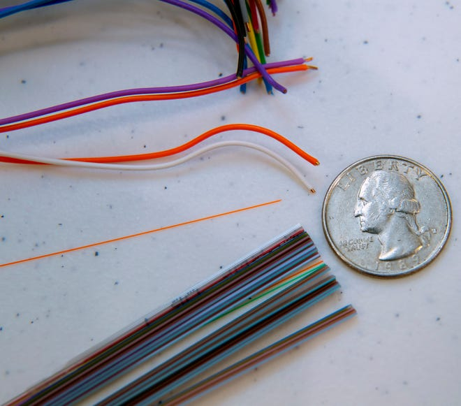 Two strands of traditional copper wire (top) used to connect a customer to the internet are shown compared with a single strand of fiber-optic cable. The fiber could provide a customer with 1,000 megabit per second downloads and uploads, while the copper wire would only handle about a 5 Mbps download and a 1 Mbps upload, barely usable for many customers.