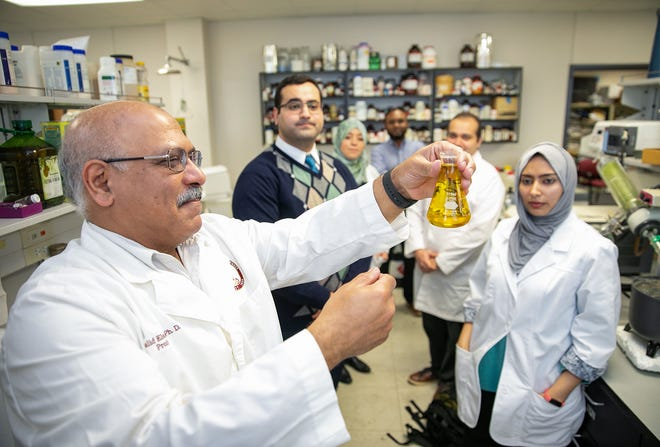 University of Louisiana Monroe College of Pharmacy Professor Khalid El Sayed, Ph.D., left, discusses with graduate students the potential of olive oil in cancer treatments. A U.S. Patent was awarded to the UL System Board of Supervisors based on El Sayed's research.