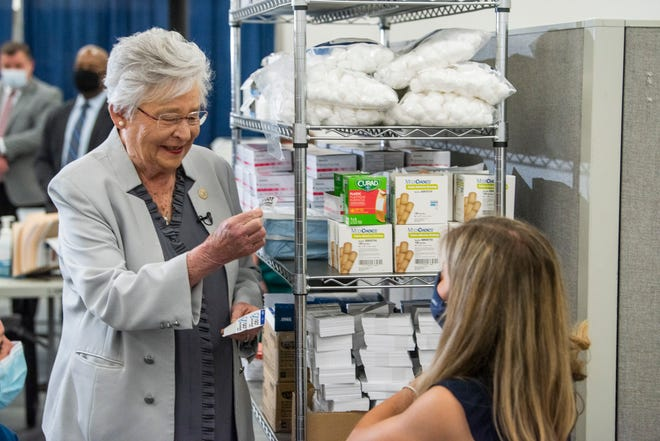 Gov. Kay Ivey hands a vaccination sticker to Auburn student Caroline Keim at EAMC COVID-19 vaccination clinic in Auburn, Ala., on Tuesday, April 20, 2021.