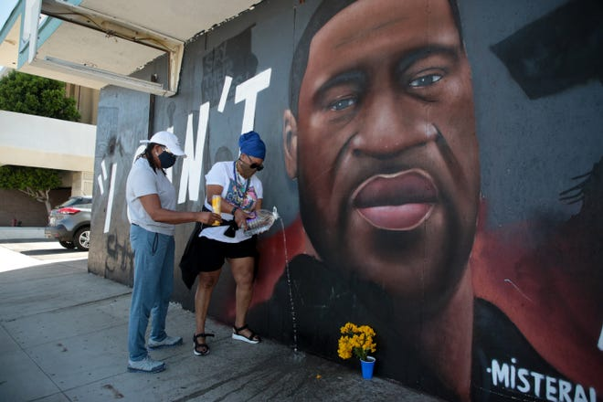 """D Pepper Massey, left, and Asanti Love, right, light candles and pour water to honor George Floyd in front of the """"I Can't Breathe"""" mural in downtown Palm Springs Tuesday.  Ex-police officer Derek Chauvin was convicted of killing Floyd minutes prior. The water is a symbol, Massey said, because """"all life started in water."""""""