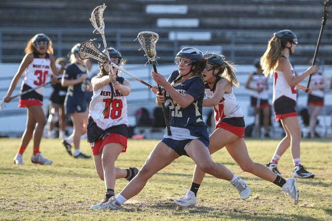 Gulf Breeze's Lauren Thompson (22) slams on the brakes as West Florida's Leah Gummere (18) and Reagan Daniels (14) close in on her in the District 1-1A championship game at West Florida High School on Monday, April 19, 2021. Gulf Breeze won 18-2.