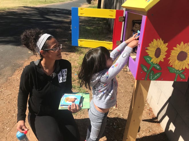 A child reaches for a book at a recently installed Little Free Library placed at Mariposa Park in Phoenix.