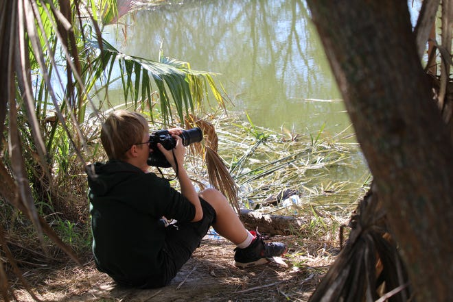 A child takes photos of wildlife near his home. An app called I-Naturalist allows anyone to share their observations with a worldwide data-gathering organization.