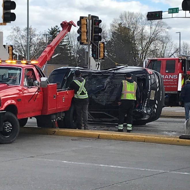 Emergency personnel work to right a squad car involved in a crash at Eighth Street and Riverview Expressway Tuesday morning.