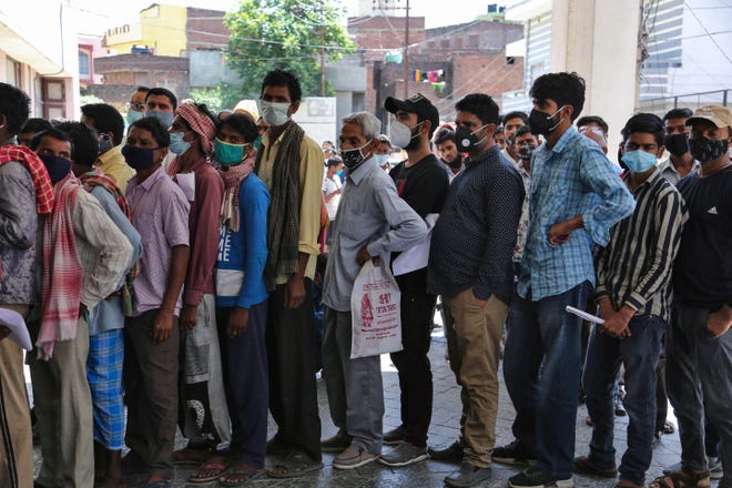 People wear face masks but do not practice physical distancing in line to get COVID-19 tests at a government hospital in Jammu, India.