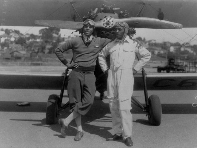 Col. Hubert Julian, left, known for his daredevil parachute jumping, and his assistant, Lt. William J. Powell, are photographed in front of their Bellanca plane at San Diego, California, April 2, 1932, in which they will attempt a nonstop flight from New York to India in August.