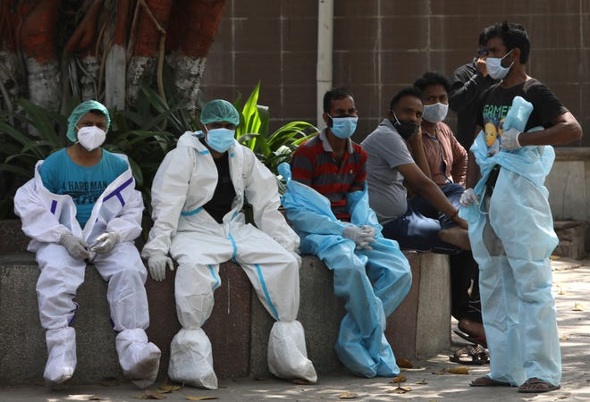 Health workers rest in between cremating COVID-19 victims in New Delhi, India, April 19, 2021.