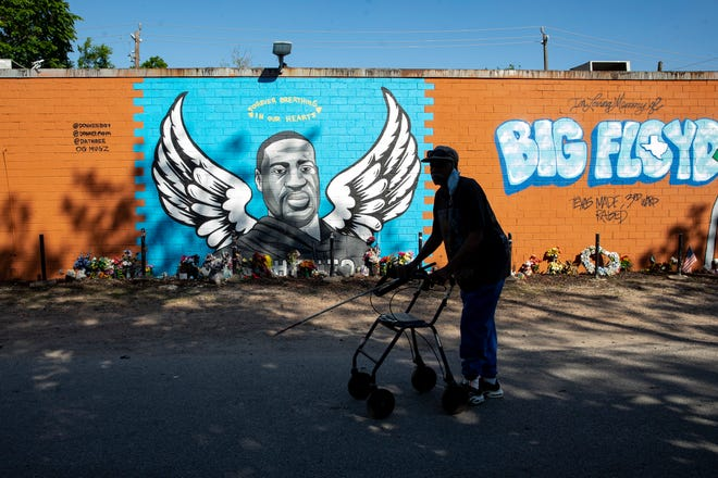 A man walks past a mural honoring George Floyd on Scott Food Store in Houston Texas's third ward after the conviction of Derek Chauvin in the killing George Floyd on Tuesday, April 20, 2021.