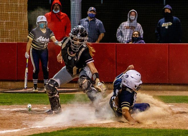 Akins' Del Loya slides safe at home to beat the tag by Lake Travis Cavaliers' Jami Watson for the winning score in Akins' 12-11 win at the District 26-6A softball game April 20 at Lake Travis High School.