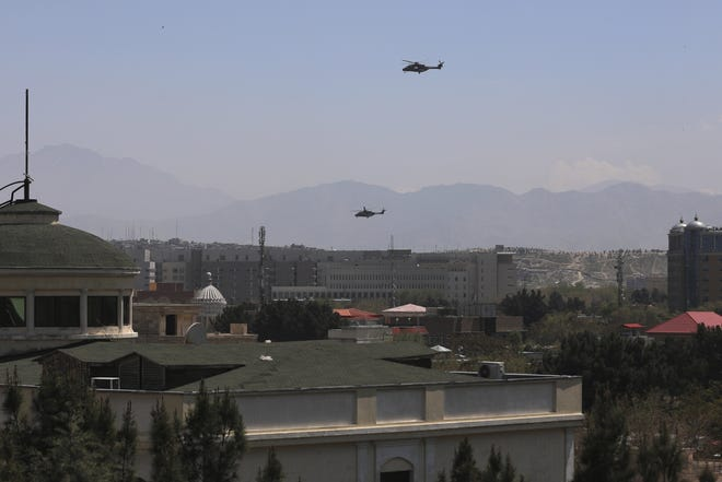 U.S. Black Hawk military helicopters fly over the city of Kabul, Afghanistan, Monday. [AP PHOTO/RAHMAT GUL]