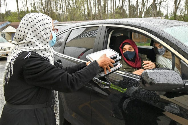Volunteer Wasima Sheikh, left, offers iftar meals April 14 to Nazneen Vahora, center, and her cousin, Anam Vahora, right, both of Ellicott City, at the Islamic Society of Baltimore in Windsor Mill. (Amy Davis/Baltimore Sun/TNS)