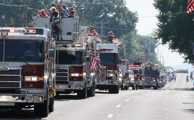A long line of emergency vehicles from Stow and the surrounding communities make their way along the parade route at the Stow Fourth of July parade in 2018. The parade was canceled last year because of the pandemic, and is returning this year on a smaller, modified scale.