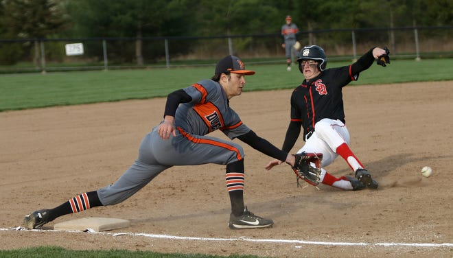 Marlington's Jack Anderson, left, reaches for the throw from home as Salem's Lane Rhodes slides into third base before heading home on a overthrow during conference play at Marlington High School Tuesday, April 20, 2021. Ed Hall Jr, Special to The Review