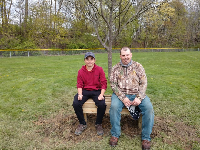 Landon Blevins, who was working on his Eagle Scout project, sits on a wooden bench at Early Park in Alliance with his father, Ben Blevins. The bench they're sitting on was first bench put into place as part of Blevins' effort on April 17.