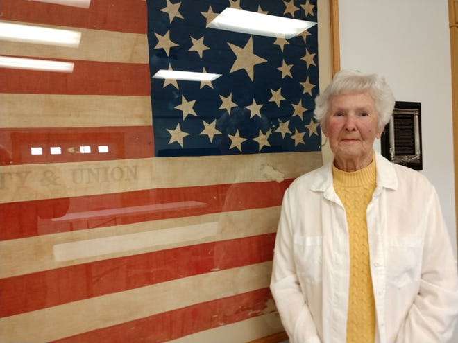 Jeanne Griffin, who was named Volunteer of the Year by the Ohio Museum's Association in early April, poses before one of the most coveted pieces in the Cleo Redd Fisher Museum in Loudonville. The 1862 American Flag was in force for only a short time, between ther statehood admissions of Kansas and West Virginia during the early Civil War.