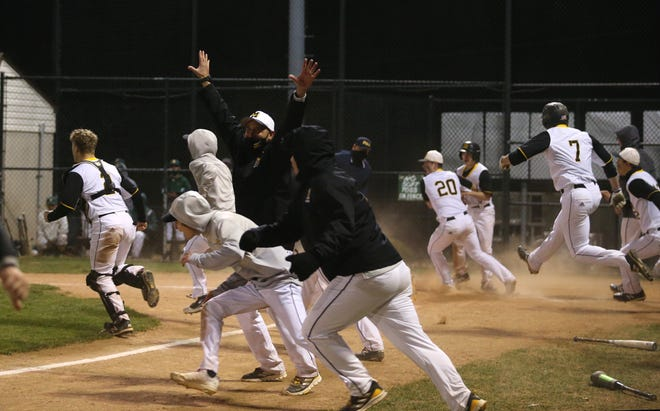Montour's dugout storms Brock Janeda after he drove in Tony Markulin on a double in the bottom of the tenth ultimately defeating Blackhawk 9-8 Tuesday night at Burkett Complex.