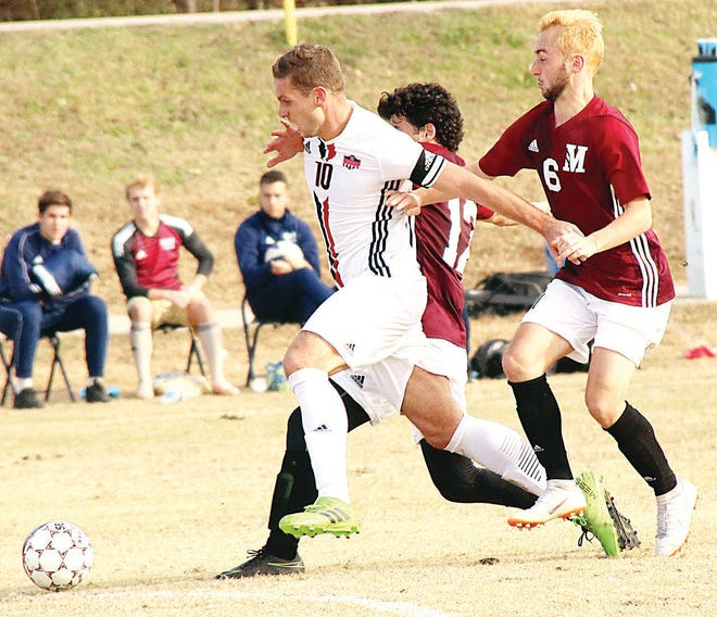 Oklahoma Wesleyan's Stefan Lukic, left, outhustles opponents to the ball during men's soccer action in a previous season.
