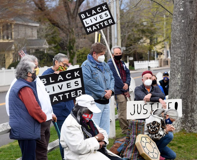 Participants bow their heads and kneel as they can during a demonstration of Black Lives Matter at the Falmouth Village Green Wednesday evening.