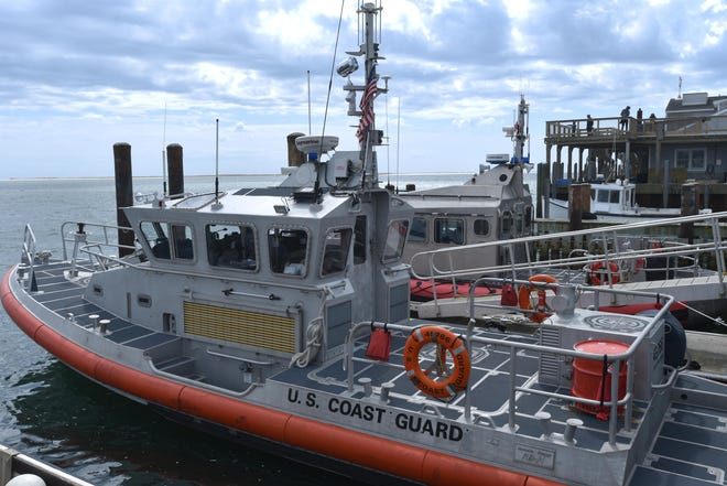 A new 45-foot Coast Guard boat, foreground, is now docked at the Chatham Fish Pier next to the old 42-foot boat it will replace. The old boat was specially designed for the surf conditions off Chatham.
