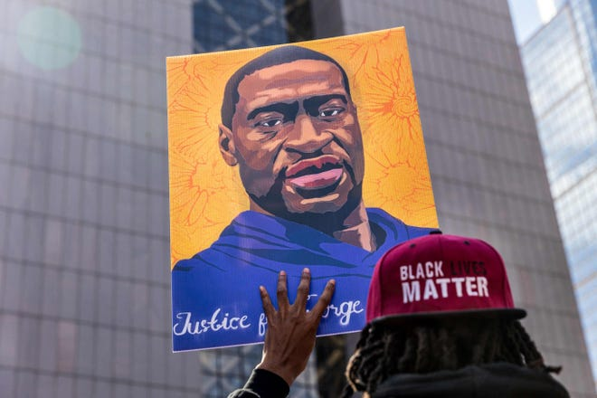 Demonstrators hold signs honoring George Floyd and other victims of racism as they gather during a protest outside Hennepin County Government Center in Minneapolis, Minnesota.
