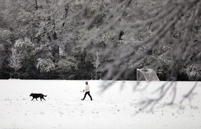 Kathi Pizzurro walks through a field at Whetstone Park on Wednesday with her dog Maddie following a heavy snowfall overnight.